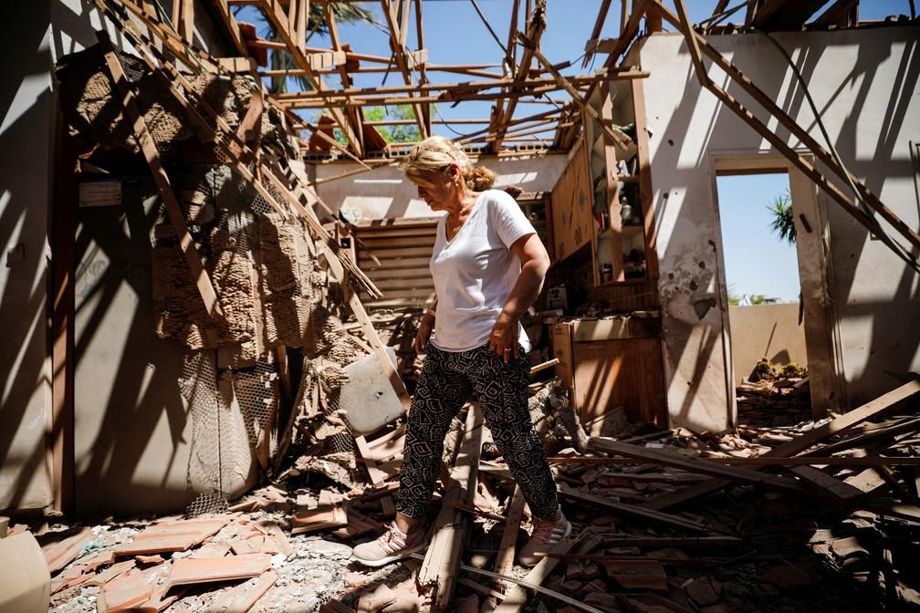 Rachel El-Gazar caminha dentro de sua casa que foi destruída após um disparo de foguete de Gaza em direção a Israel na cidade de Sderot, no sul do país, no sábado (15)   — Foto: Amir Cohen/Reuters