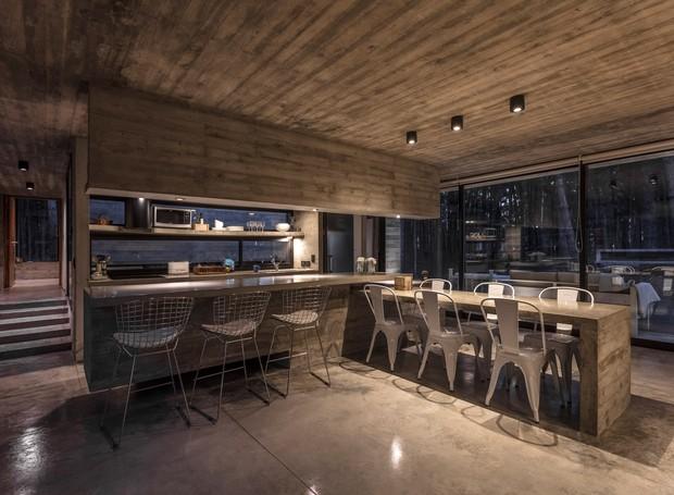 O concreto dá forma a diversas estruturas como a mesa de jantar e o balcão da cozinha (Foto: Federico Kulekdjian)