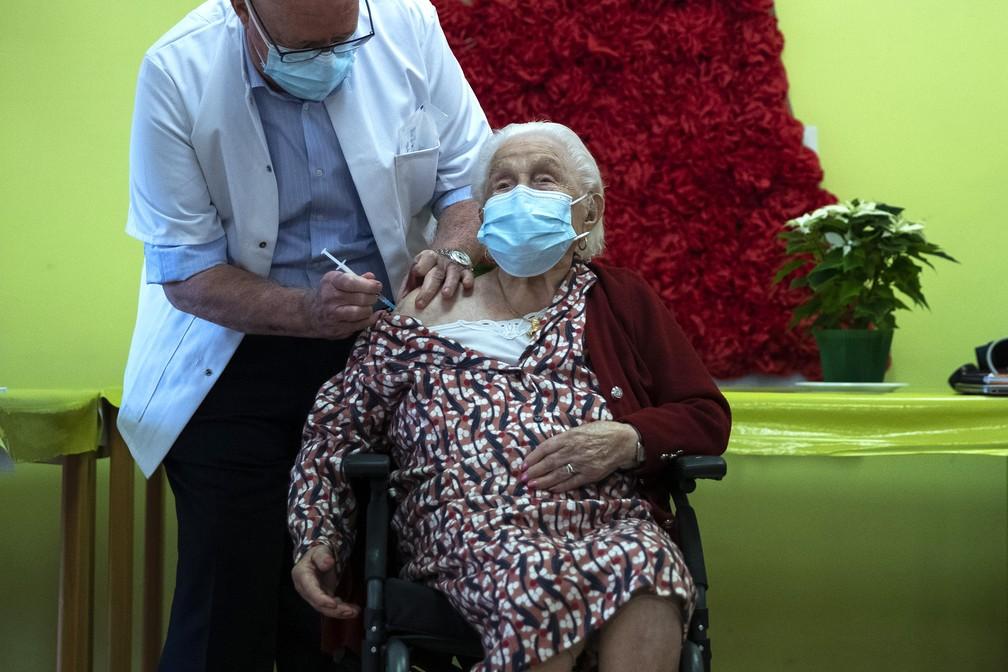 Josepha Delmotte, de 102 anos, recebe a primeira dose da vacina da Pfizer/BioNTech contra a Covid-19 em Mons, na Bélgica, nesta segunda-feira (28). — Foto: Francisco Seco/Pool/AFP