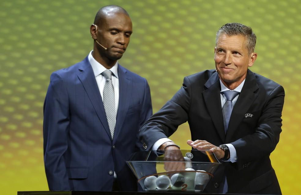 Abidal e Michael Heselschwerdt, diretor de competições de clubes da Uefa, no sorteio da Liga Europa (Foto: AP Photo/Claude Paris)