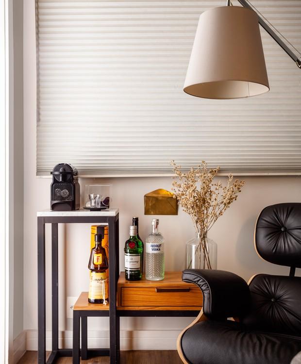 Mesas de apoio criadas pelo arquiteto dão origem ao espaço que é minibar e canto de leitura. Poltrona Eames da Abracasa, luminária Tolomeo de piso da Dimlux (Foto: Dhani Borges)