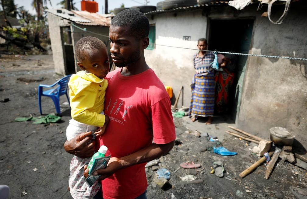 Nelson Vasco, morador de Beira, com a filha do lado de fora de casa. — Foto: Reuters/Mike Hutchings TPX Images of the Day