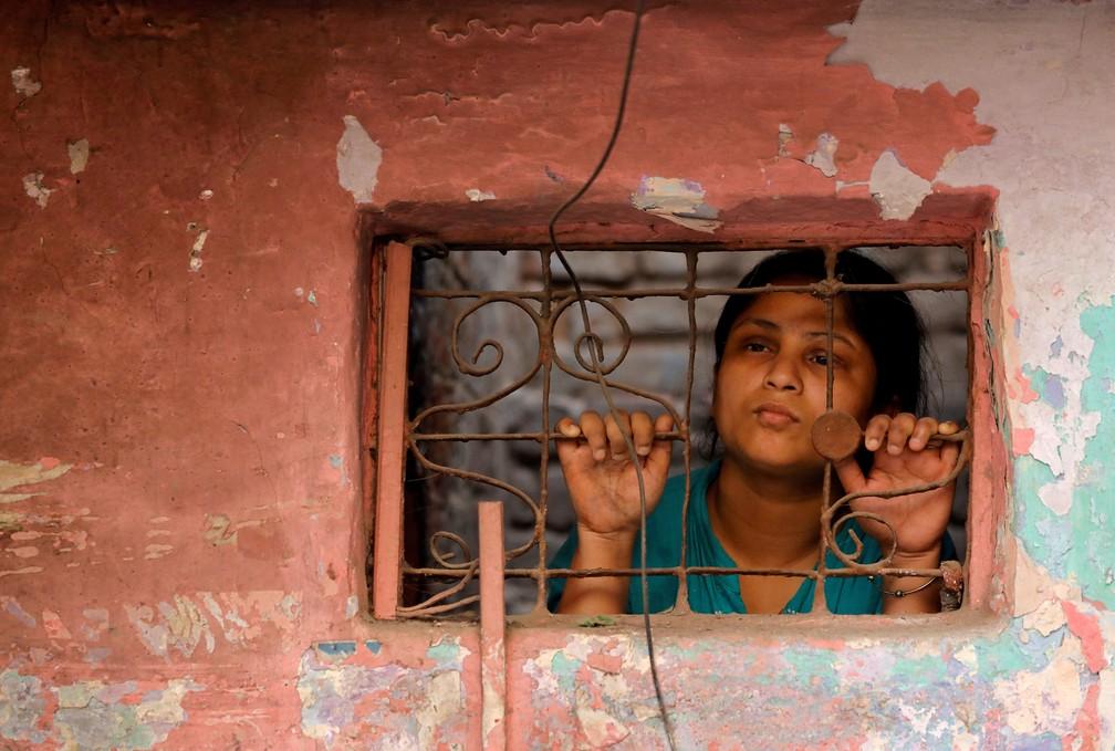 30 de abril - Uma mulher olha através das grades da janela de sua casa, em Nova Deli, na Índia — Foto: Anushree Fadnavis/Reuters