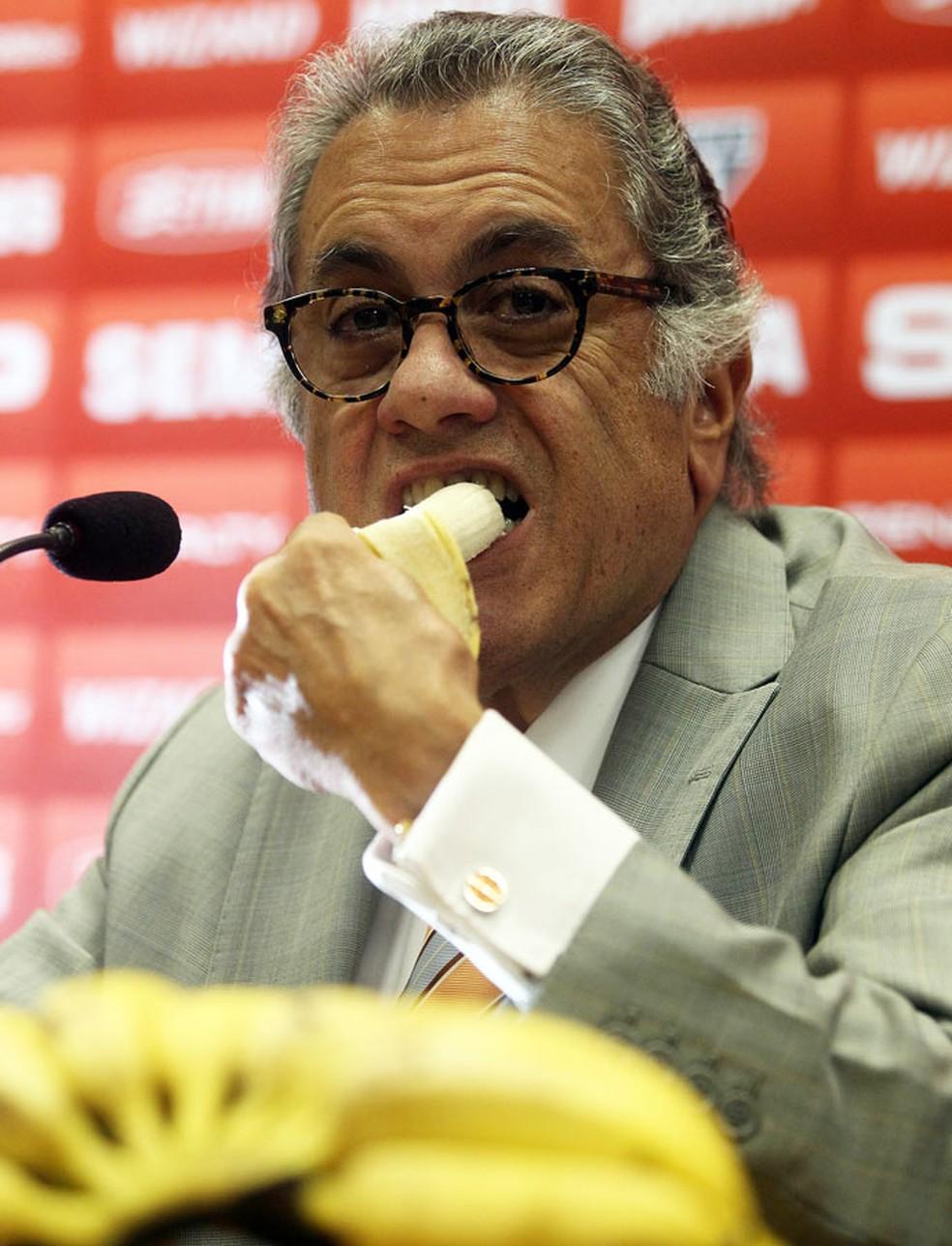 """Carlos Miguel Aidar come banana durante coletiva do São Paulo em 2014, na qual acusou o Palmeiras de estar """"se apequenando"""" — Foto: Felipe Rau/Agência Estado"""