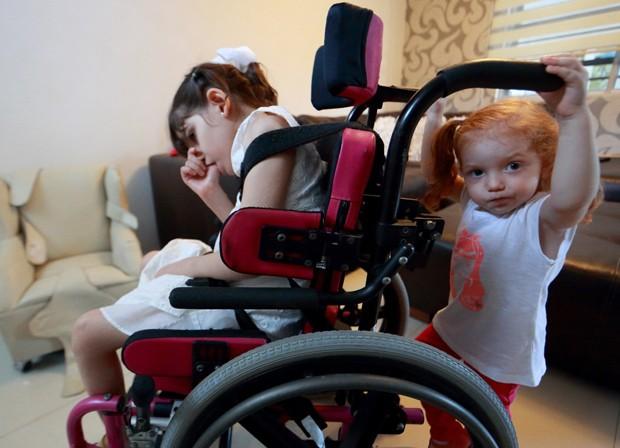 Garota Graciela Elizalde (dir.) e sua irmã Valentina brincam em sua casa: Graciela passará a receber remédio a base de maconha  (Foto: AFP Photo/Carlos Ramirez)