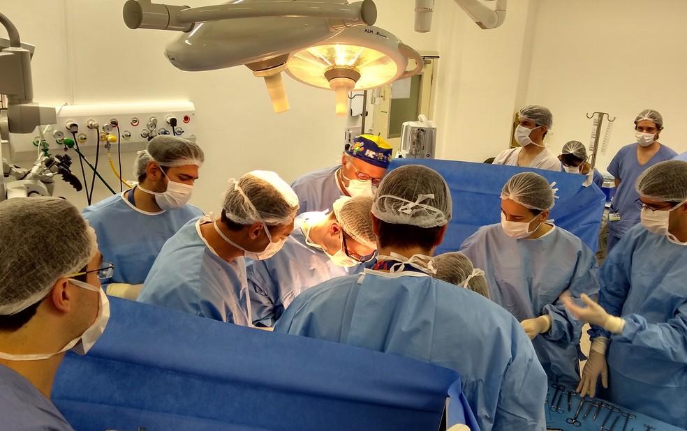 De touca amarela e azul, o chefe da equipe, Hélio Machado, acompanha a cirurgia das gêmeas siamesas em Ribeirão Preto, SP  (Foto: Divulgação/HC-FMRP/USP)