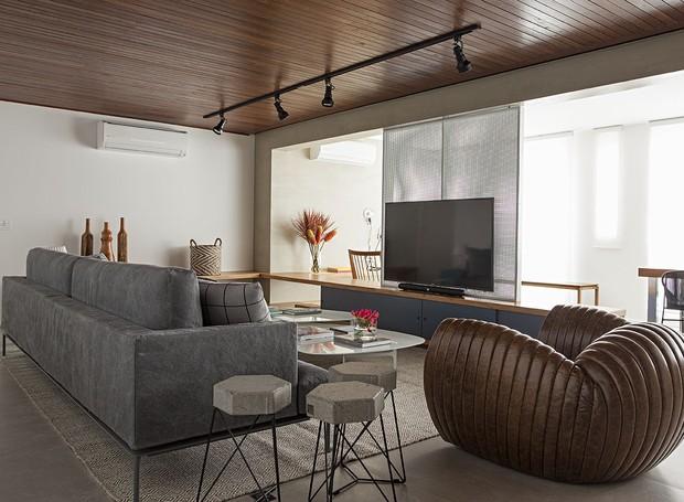 A sala de TV faz bom uso do forro de cumaru, que deixa os sons mais agradáveis. Sofá e poltrona do Estudiobola (Foto: Gui Morelli/Divulgação Produção: Núria Uliana)