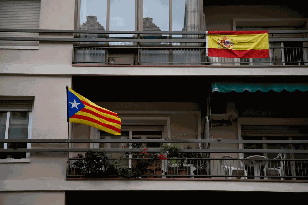 Vizinhos exibem em suas sacadas bandeiras da Catalunha (à esquerda) e da Espanha em prédio em Barcelona  (Foto: Bob Edme/AP)