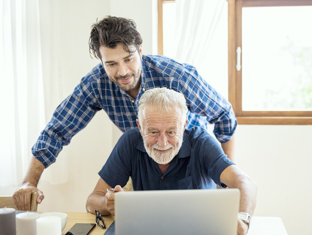 Smiling elderly father and son rest on weekend laugh using internet happy together at home. (Foto: Getty Images)