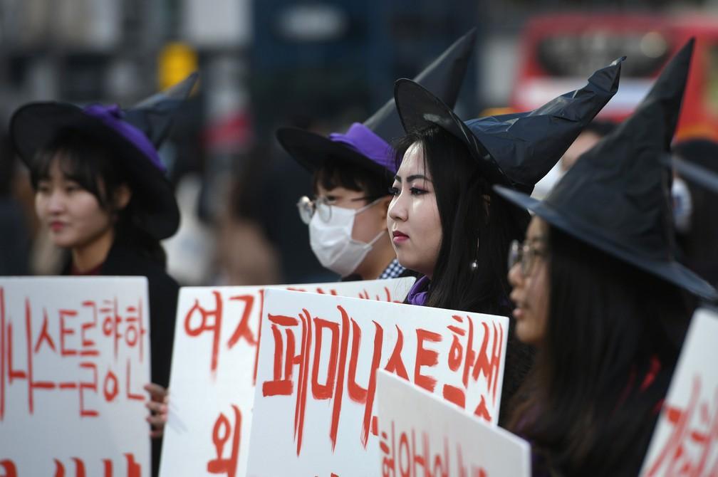 Sul-coreanas com chapéus de bruxas participam de manifestação em Seul, nesta sexta-feira (8), Dia da Mulher  — Foto: Jung Yeon-Je / AFP