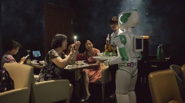 Clientes tiram foto de um robô garçom em um restaurante em Xangai (Foto: YUYANG LIU / NYT)