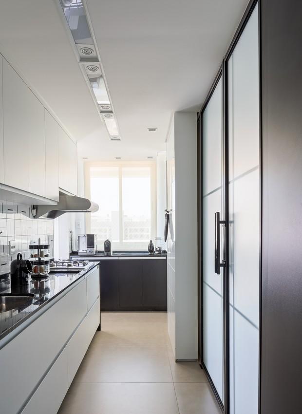 A cozinha do tipo corredor ganhou porcelanato de grande formato no piso e azulejos decorativos no frontão (Foto: Haruo Mikami/Divulgação)