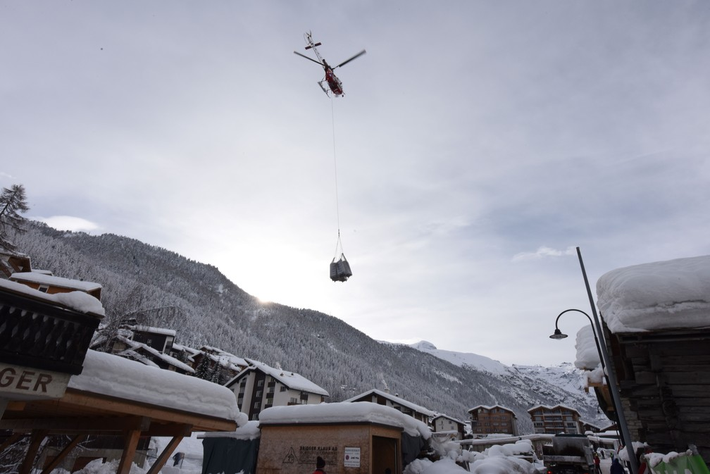 10 de janeiro - Um helicóptero leva um carregamento de toalhas e roupas de cama para hotéis após fortes avalanches que deixaram mais de 13 mil turistas presos em Zermatt, uma das estações de esqui mais populares da Suíça. A neve bloqueou todas as estradas e ferrovias até o resort (Foto: Mark Ralston/AFP)