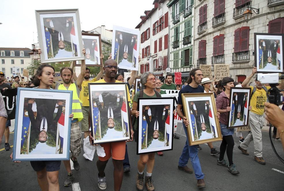 Manifestantes carregam retratos de cabeça para baixo do presidente francês Emmanuel Macron durante protesto pelas ruas de Bayonne, na França, neste domingo (25) — Foto: Bob Edme/AP