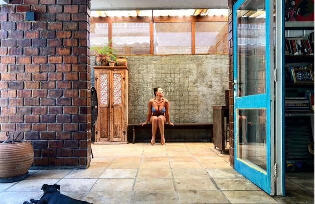 Fabiula Nascimento posa na varanda com um de seus cachorros em primeiro plano (Foto: Reprodução/Instagram)