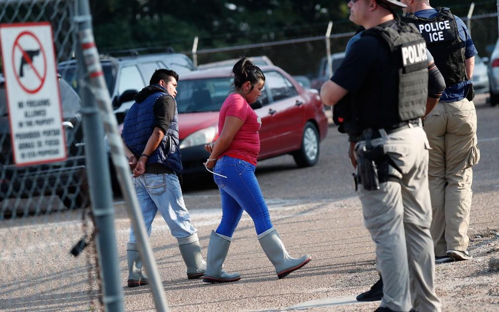 Duas pessoas são detidas por agentes de imigração em fábrica da Koch Foods Inc. em Morton, Mississippi, na quarta-feira (7) — Foto: AP Photo/Rogelio V. Solis