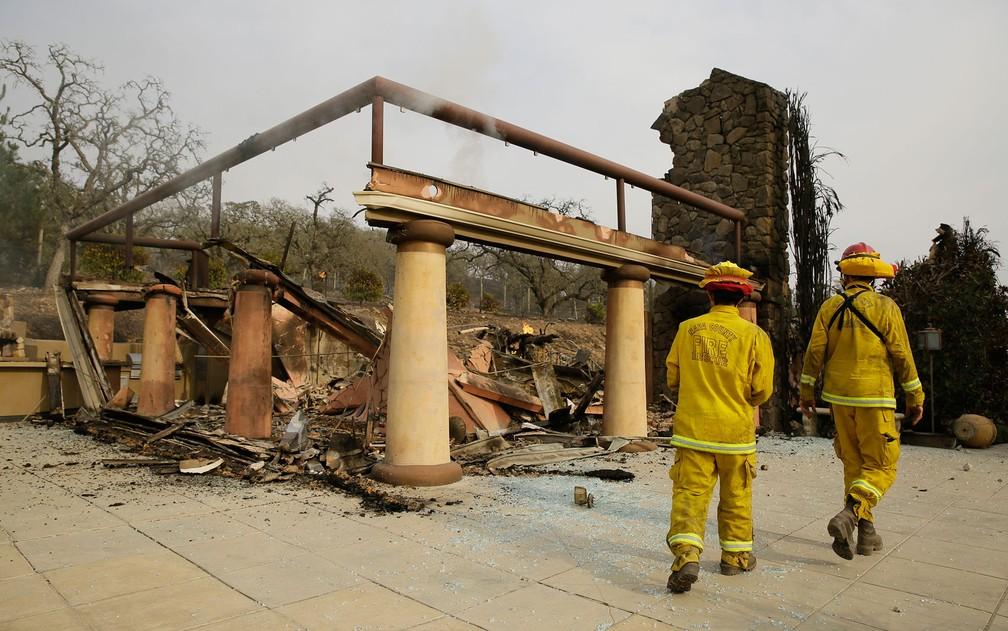 Bombeiros caminham entre as ruinas do prédio principal da vinícola Signorello, em Napa, na Califórnia, destruído por incêndio, em foto de 10 de outubro (Foto: AP Photo/Eric Risberg)