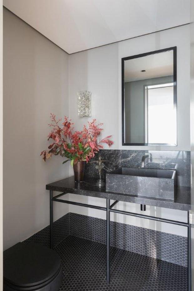 O lavabo ficou mais chique com o preto onipresente. No piso, as pastilhas hexagonais avançam 30 cm sobre as paredes, dando forma ao rodapé que mais parece uma moldura (Foto: Alexandre Disaro/Divulgação)