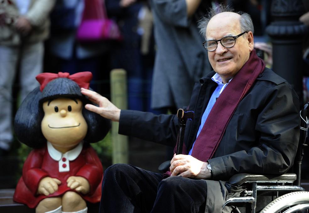 O cartunista Joaquin Salvador Lavado, também conhecido como Quino, posa ao lado de uma escultura de sua personagem Mafalda, em Oviedo, na Espanha. Foto de outubro de 2014 — Foto: Miguel Riopa/AFP/Arquivo