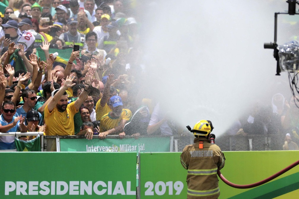Bombeiros refrescam público em frente ao Palácio do Planalto, em Brasília (DF), antes da cerimônia de posse do presidente — Foto: Fátima Meira/Futura Press/Estadão Conteúdo