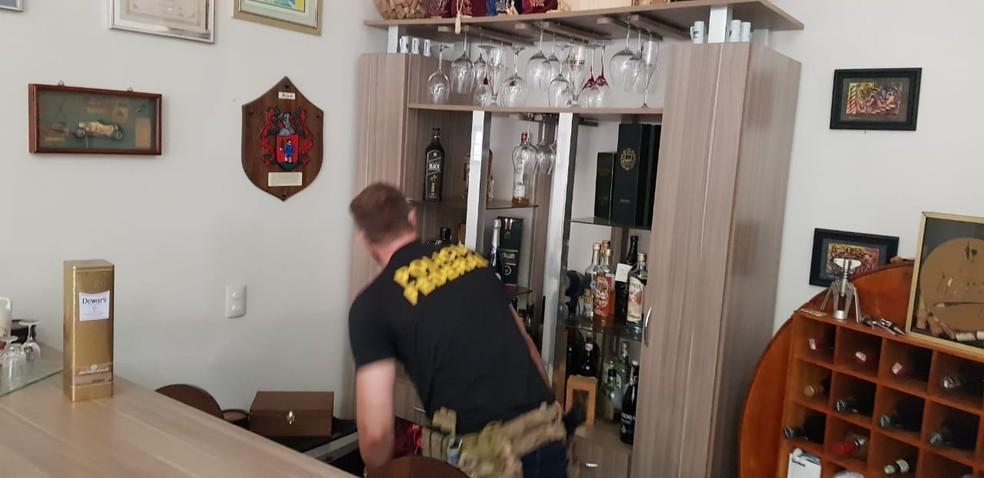 Policial cumpre mandado de busca em residência, na operação Reciclagem — Foto: PF/Divulgação