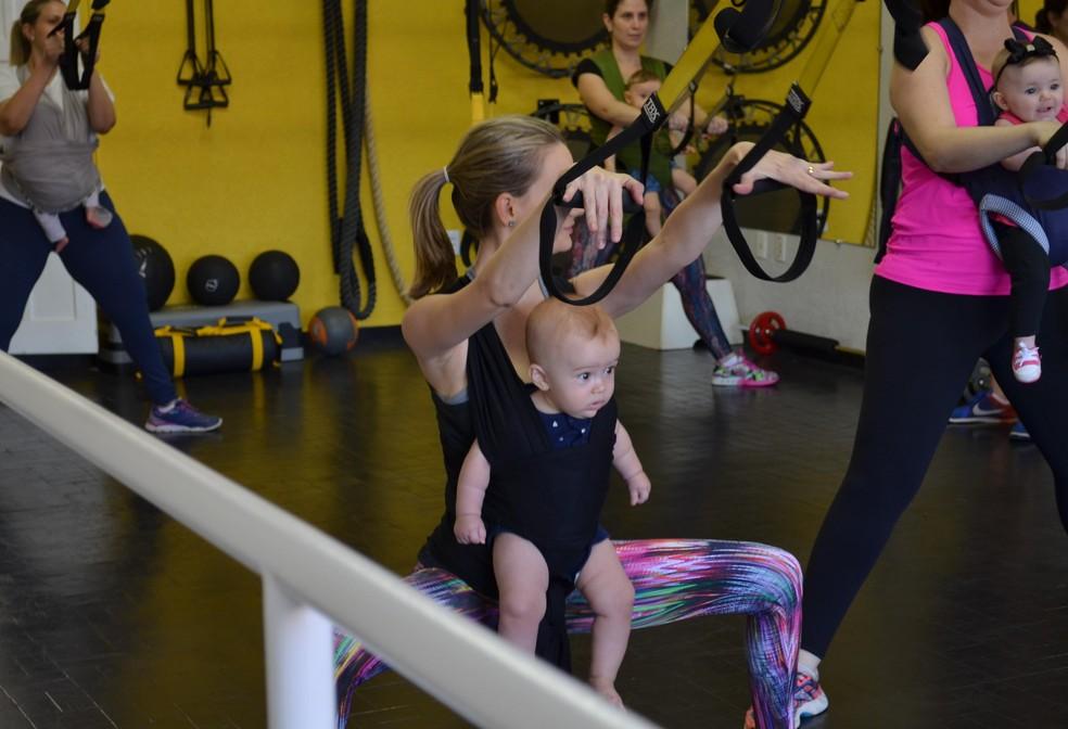 Crianças ficam presas nas mães por um sling para maior segurança durante a atividade em academia de São Carlos (Foto: Ana Marin/EPTV)