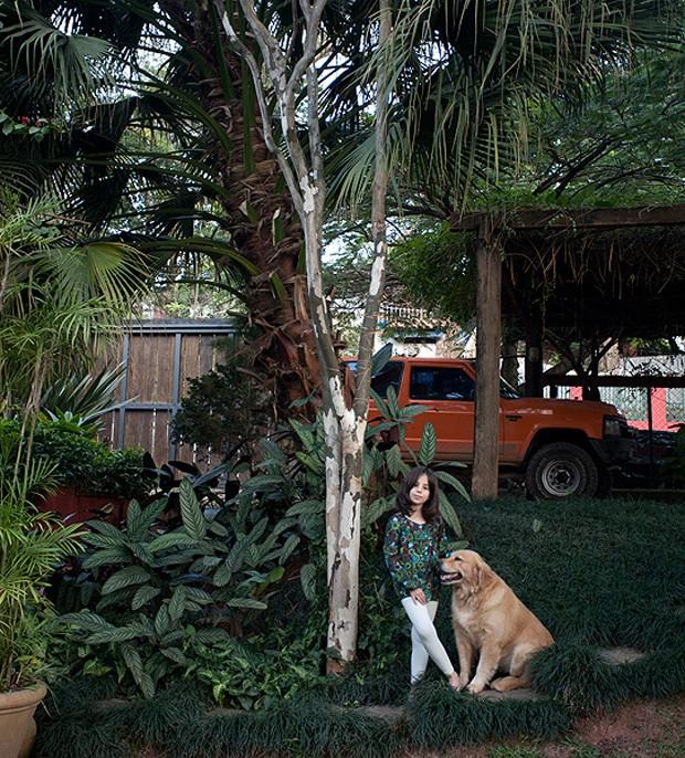 Teodora, filha da arquiteta Kita Flórido, ao lado do seu cachorro de estimação e da árvore pau-ferro, localizada no jardim de sua casa. Espaços assim são ótimos para cães de grande porte (Foto: Pedro Abude / Editora Globo)