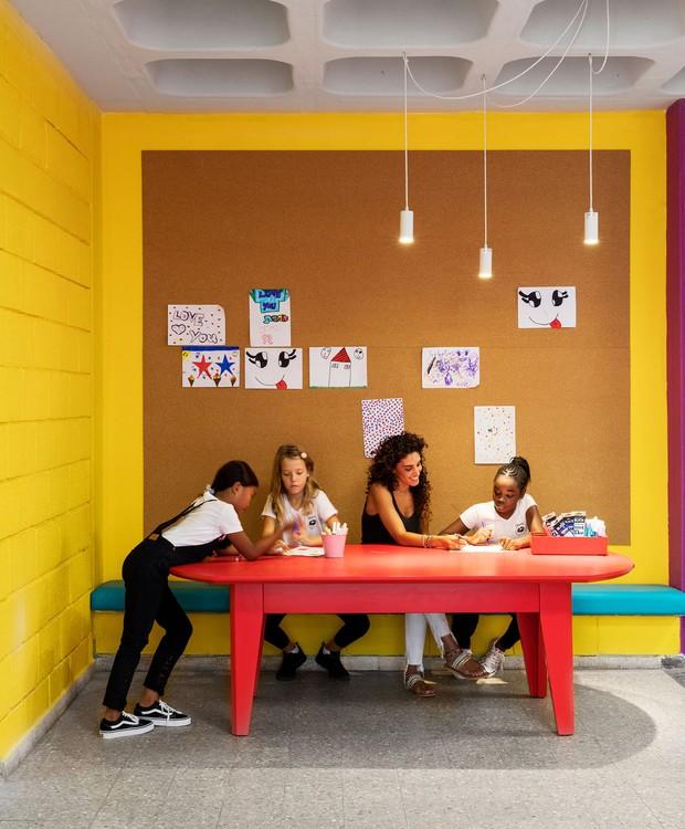 Murais de cortiça exibem os desenhos das crianças. Áreas de aprendizado foram instaladas nos locais de circulação para que os pequenos possam interagir livremente e experimentar novas formas de ensino (Foto:  Itay Benit/ Dezeen/ Reprodução)