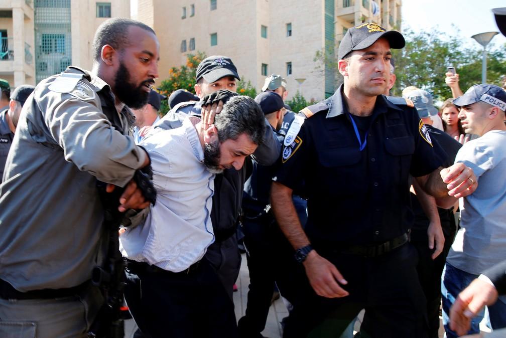 Polícia detém homem do lado de fora do prédio em que embaixada americana foi inaugurada nesta segunda-feira (14) (Foto: Ammar Awad/Reuters)