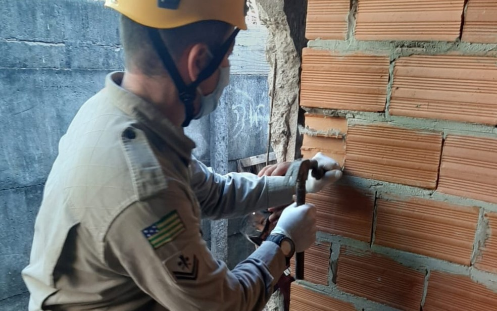 Bombeiros usam entalhadeira e martelo para retirar tijolos e libertar criança — Foto: Reprodução/Corpo de Bombeiros