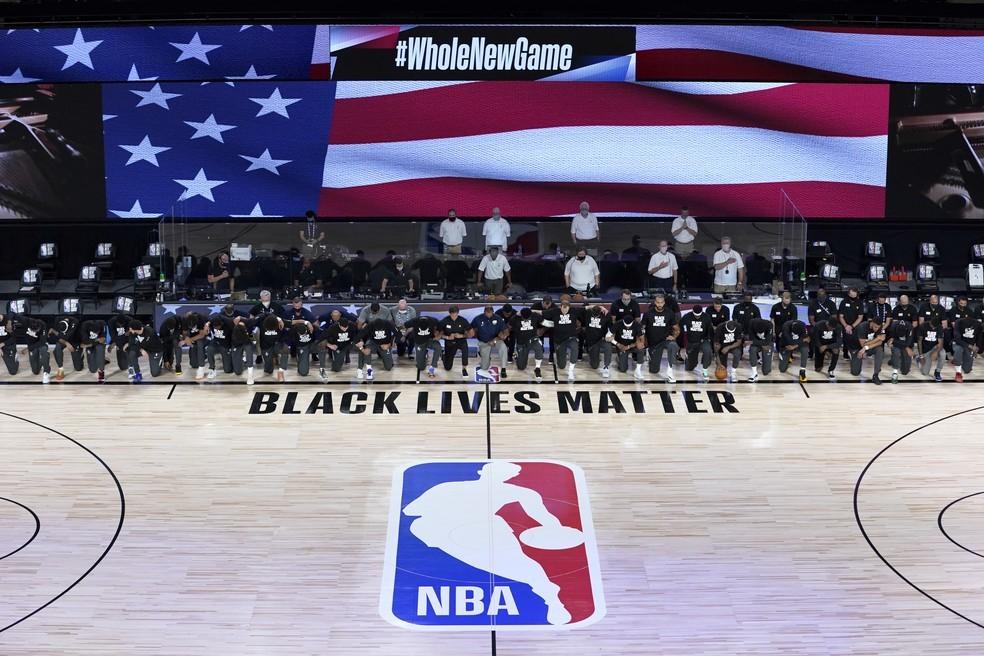 Jogadores e comissões técnicas de Utah Jazz e New Orleans Pelicans se ajoelham antes de reabertura da NBA — Foto: Ashley Landis / Pool Photo