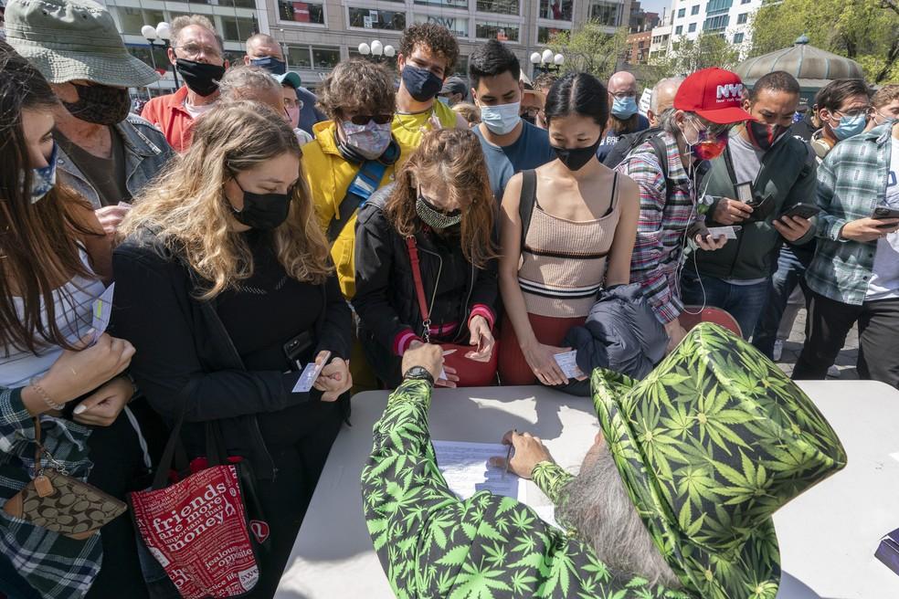 """Homem com fantasia de cannabis distribui cigarros de maconha durante o evento """"Joints for Jabs"""", em 20 de abril de 2021, em Nova York — Foto: Mark Lennihan/AP"""
