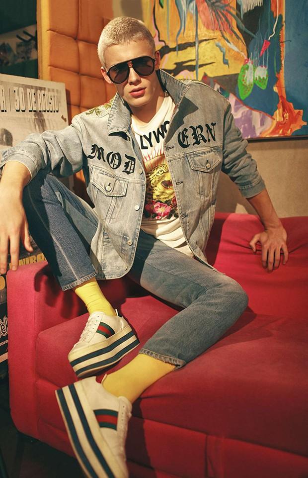 João Knorr, modelo, usa jaqueta jeans, camiseta, calça jeans e tênis Gucci; óculos de sol Fendi; meias amarelas Puket. São Paulo (cid.) - Brasil. 10/08/2017. Foto: Ivan Erik / Edições Globo Condé Nast. (Foto: GQ)