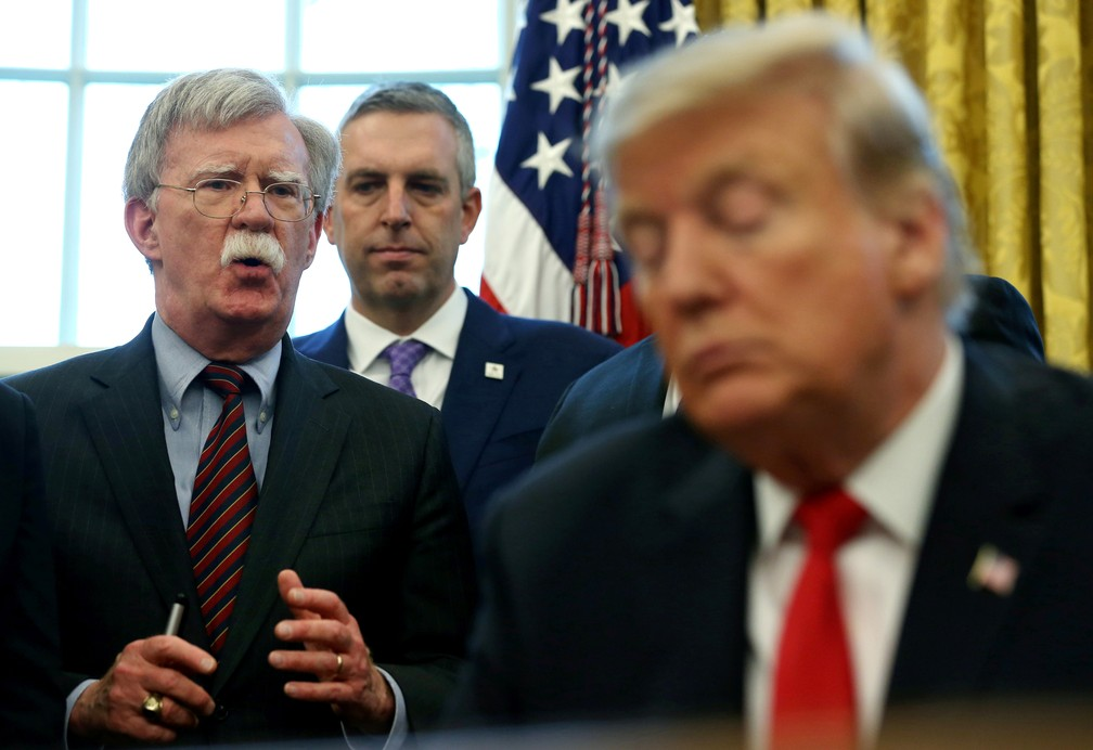 Na foto, de fevereiro de 2019, Trump aparece assinando um memorando com John Bolton, agora ex-conselheiro de segurança nacional, ao fundo (de óculos). — Foto: Leah Millis/Reuters