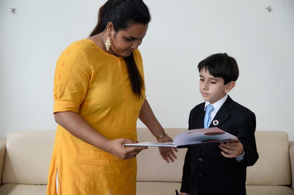 João Paulo Guerra Bezerra, brasileiro de oito anos, mostra um de seus livros publicados a Jayathma Wickramanayake, secretária geral da ONU para a Juventude, em Nova York (Foto: Divulgação/Fernanda Calfat)