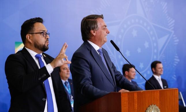 O presidente Jair Bolsonaro com o presidente da Caixa, Pedro Guimarães, e os ministros João Roma e Anderson Torres ao fundo