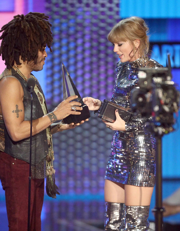 A cantora Taylor Swift recebendo um de seus troféus no American Music Awards 2018 de Lenny Kravitz (Foto: Getty Images)