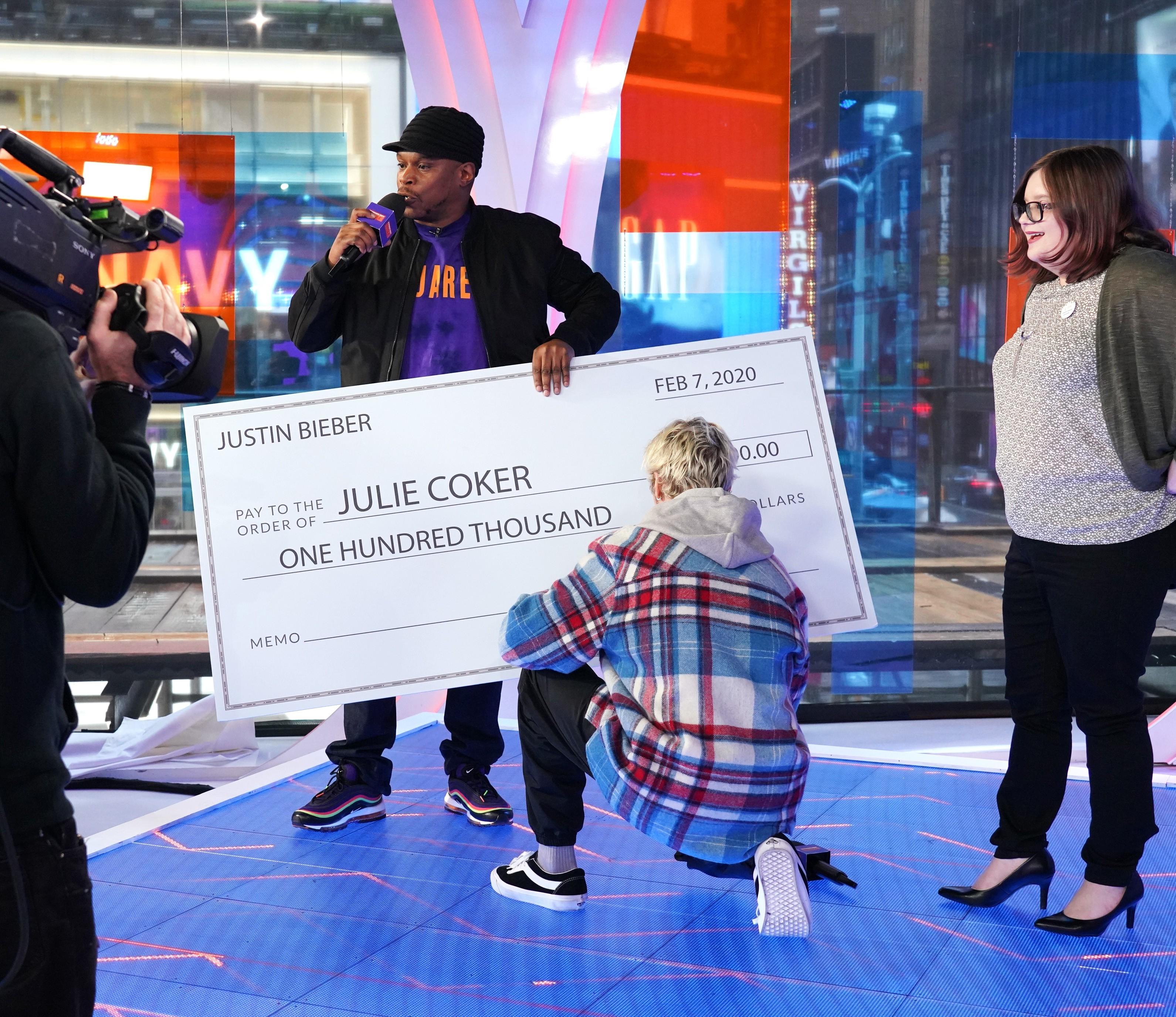 Justin Bieber assina o cheque de 100 mil dólares para Julie Coker