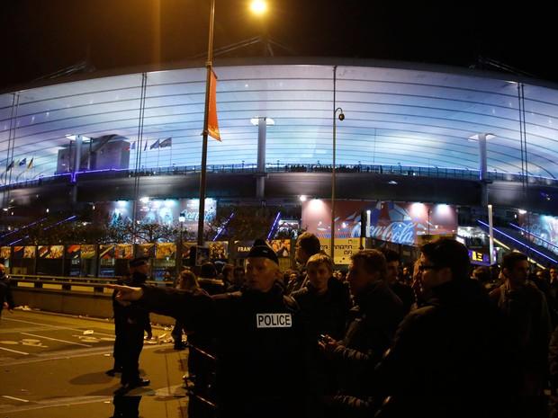 Policiais orientam as pessoas em frente ao Stade de France após ataque (Foto: Michel Euler/AP)