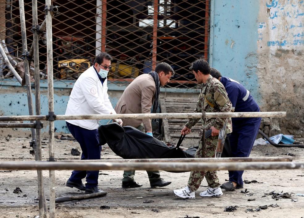 Corpo de vítima de atentado em Cabul, no Afeganistão, é carregado por afegãos nesta sexta-feira (9)  (Foto: Omar Sobhani/ Reuters)