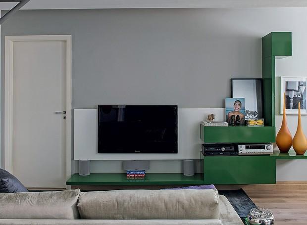 O rack desenhado pelo arquiteto Ricardo Brito oferece mais do que a funcionalidade – é também decorativo, graças à forma e à cor verde. Apesar de marcante, a peça suspensa é leve, fundamental para economizar espaço no apartamento de 72 m² (Foto: Marcelo Magnani/Casa e Jardim)