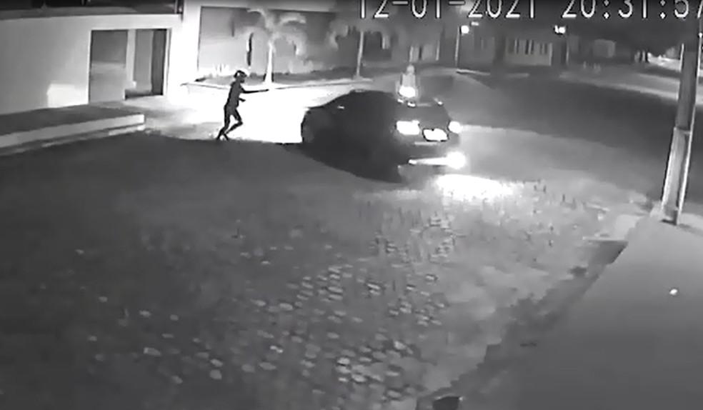 Criminoso aponta arma em direção à ex-prefeita Micarla de Sousa, enquanto ela reage a abordagem dando ré no carro. — Foto: Reprodução