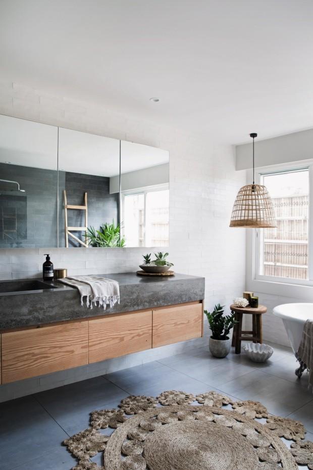 Luminária e tapete de fibras naturais, além de plantas, trazem conforto ao banheiro desta casa de fazenda na Austrália, enquanto os tijolos bom tinta branca destacam a bancada de concreto (Foto: Chris Warnes Warnes