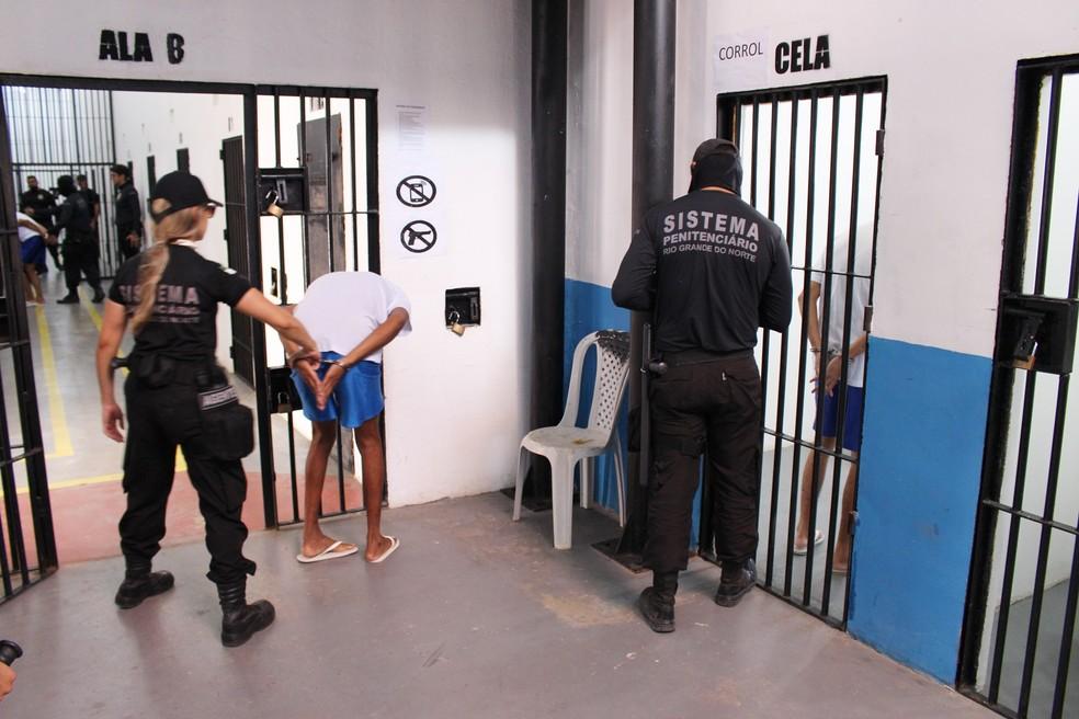 Na 'extração', presos são retirados das celas sempre algemados com as mãos nas costas — Foto: Anderson Barbosa/G1