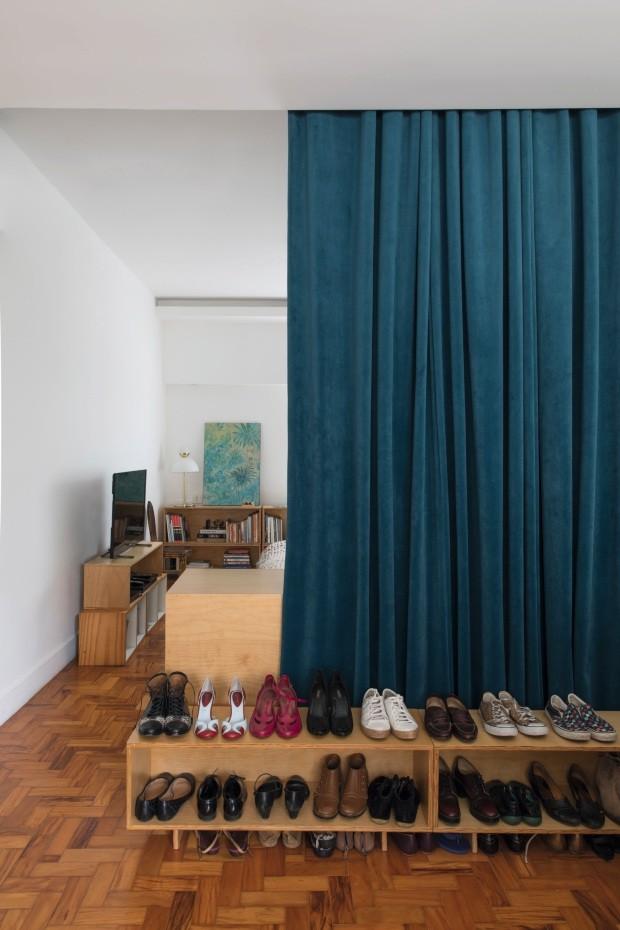 Quarto do casal e closet. Para tornar o dormitório mais acolhedor, os arquitetos instalaram uma cortina de veludo, que divide os espaços. Os sapatos ficam em módulos desenhados por Mariana (Foto: Maíra Acayaba / Editora Globo)