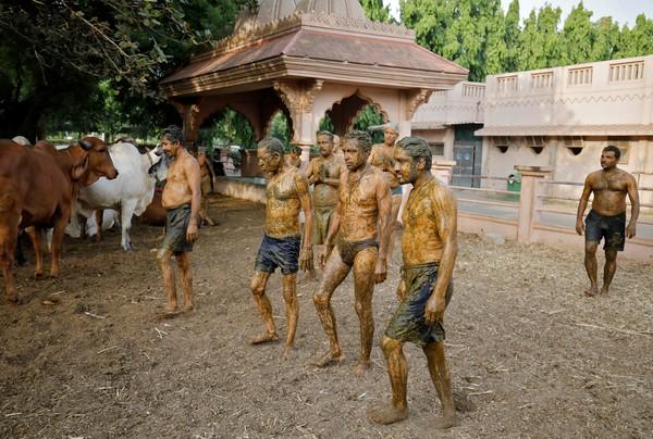 Pessoas perto de Ahmedabad, na Índia, depois de passar uma pasta de estrume de vaca no corpo, em 9 de maio de 2021 — Foto: Amit Dave/Reuters
