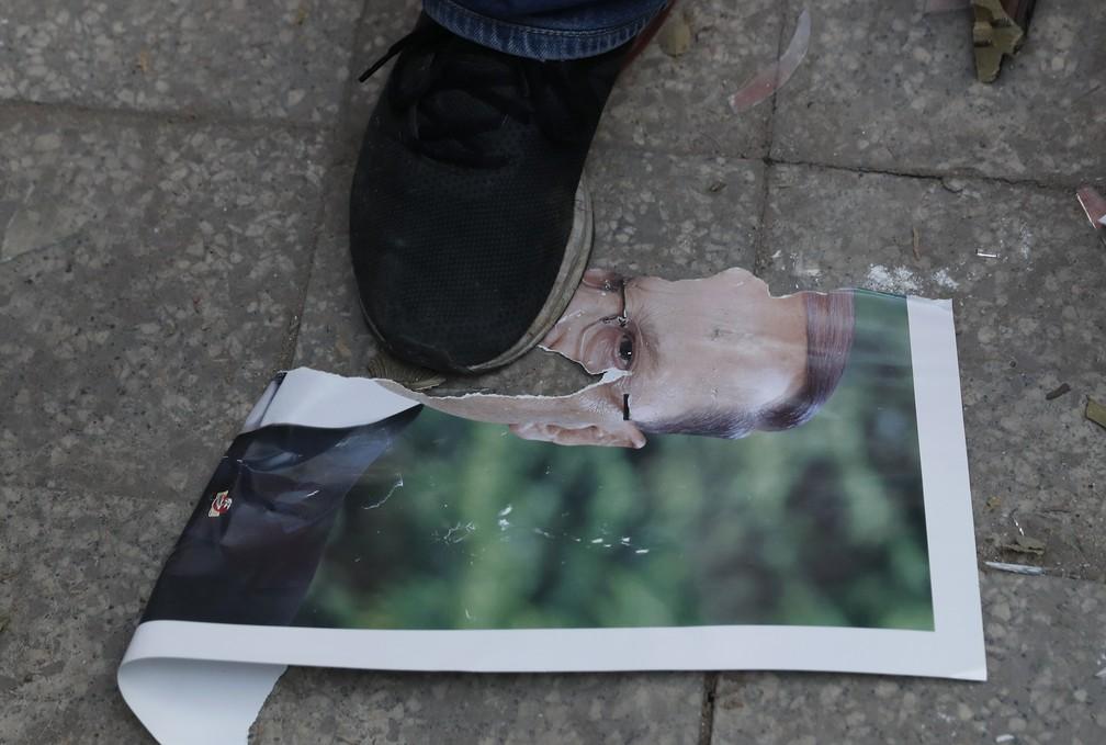 Manifestante pisa em foto do presidente do Líbano, Michel Aoun, durante protesto em 8 de agosto após megaexplosão em Beirute — Foto: Hussein Malla/AP