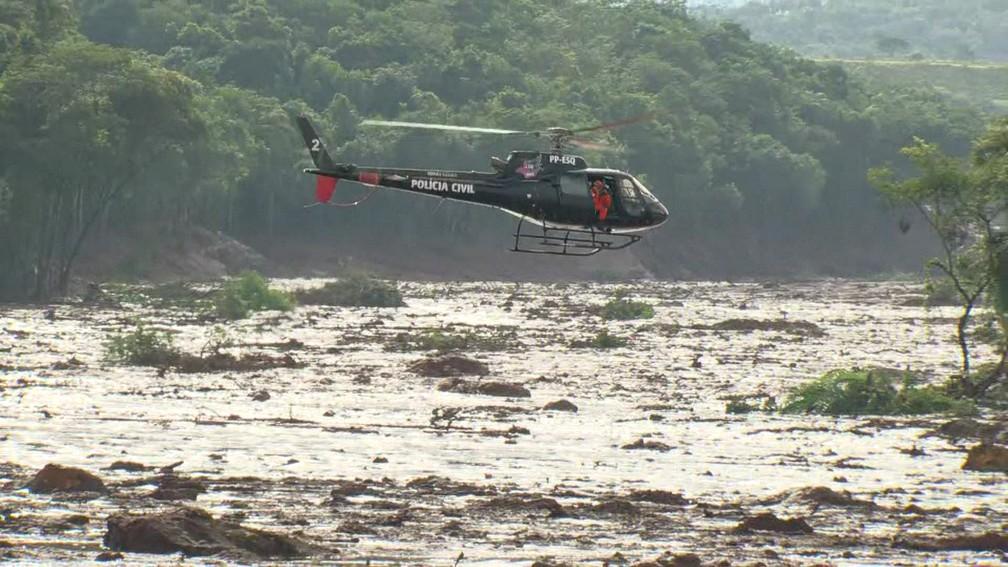 Helicóptero da Polícia Civil sobrevoa área devastada pela lama a procura de vítimas de acidente com mina da Vale em Brumadinho (MG) — Foto: Reprodução/TV Globo