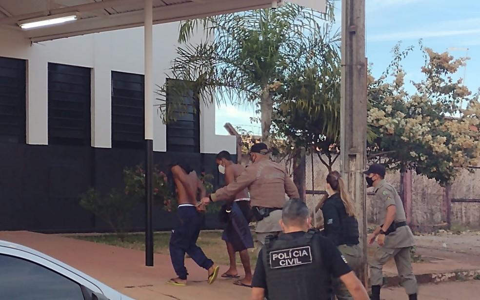 Dois presos chegam a delegacia de Águas Lindas de Goiás durante a Operação Anhanguera — Foto: Danilo Moreira/TV Anhanguera