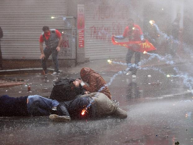 Manifestantes tentam se proteger de jatos de água e bombas de gás lacrimogêneo durante confrontos em Istambul, na Turquia. Os ativistas fizeram uma marcha de 1º de Maio desafiando a proibição de percorrer a praça Taksim, no centro da cidade (Foto: Emrah Gurel/AP)
